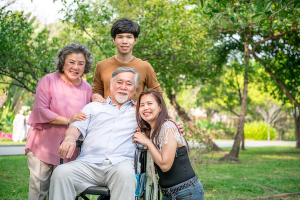 Senior man in wheel chair with his family in park