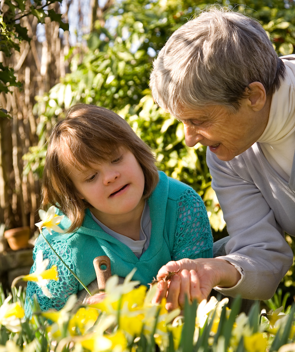 Girl with down syndrome and her grandmother in a garden